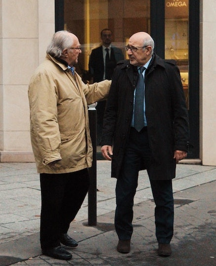 Two older men standing and talking about business